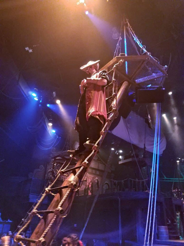Pirate's Dinner Adventure in Buena Park Orange Pirate standing on ladder